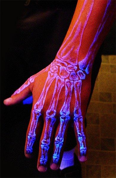 Неоновая татуировка в виде скелета на кисти руки