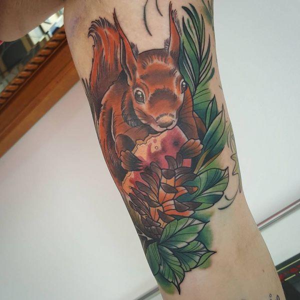 Татуировка белки с удой в руках и листьями вокруг