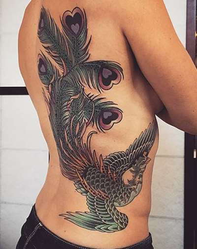Красивая птица феникс на спине у девушки