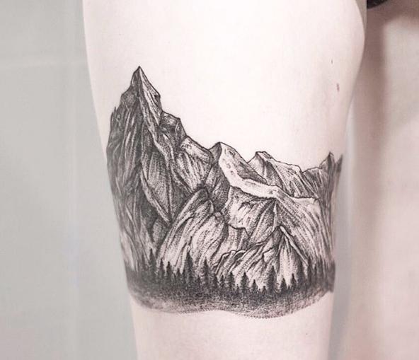 Тату горы на бедре девушки