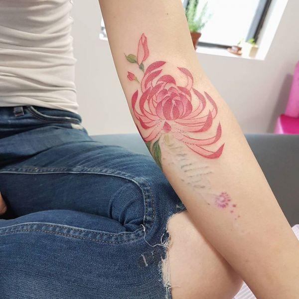 Татуировка красной хризантемы на руке девушки
