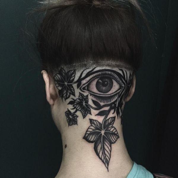 Татуировка листья и глаз на шее у девушки