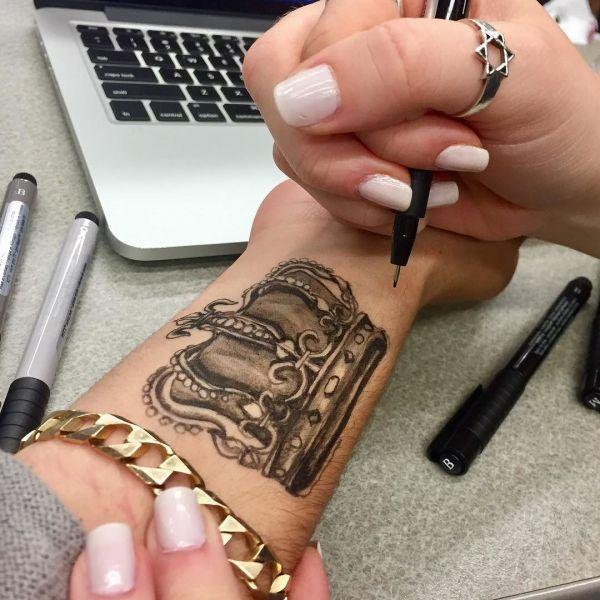 Татуировка маркером короны на руке