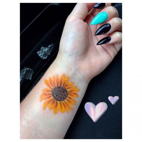 Татуировка небольшого подсолнуха на запстье девушки