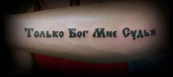 Татуировка с надписью Только Бог мне судья