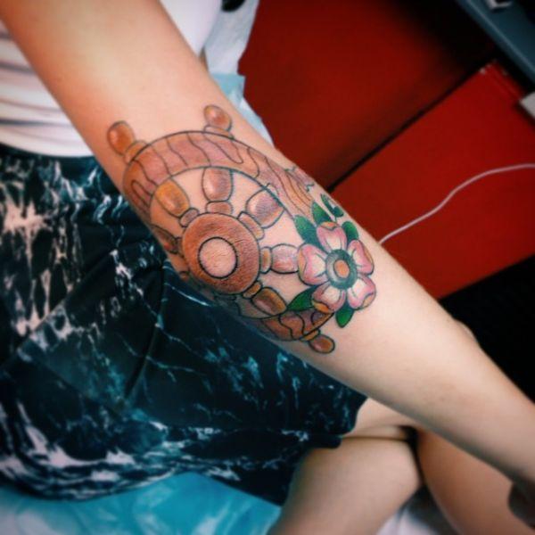 Татуировка коричневого штурвала на руке девушки