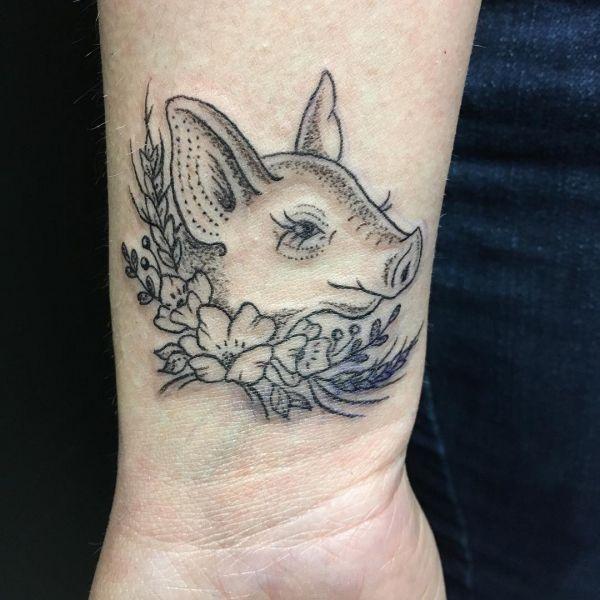Татуировка головы свиньи как контур на запястье