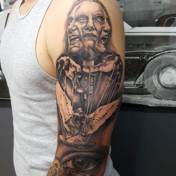 Татуировка зло на плече парня
