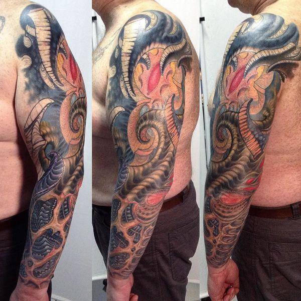 Татуировка в стиле органика на руке парня