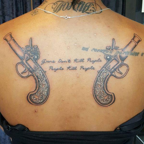Татуировка оружие в виде двух пистолетов и надписи на спине девушки