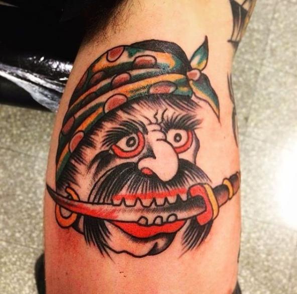 Пример тату пиратского стиля с пиратом на плече, который держит кинжал в зубах