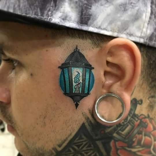 Фонарь в виде татуировки около уха у парня