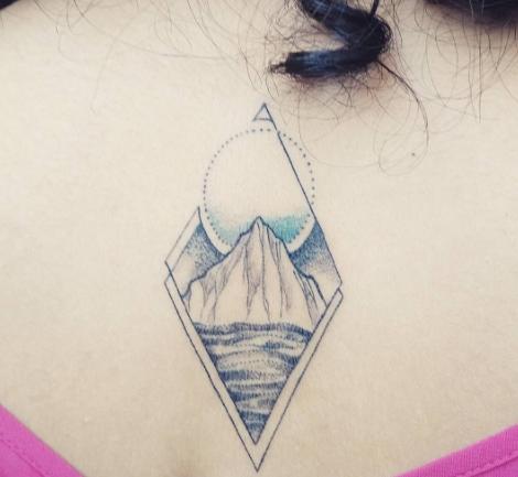 Татуировка на спине девушки в виде гор