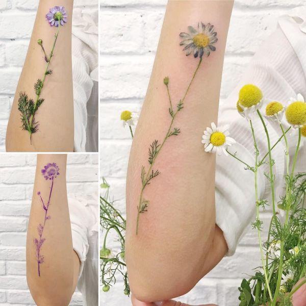 Татуировка цветка ромашки у девушки