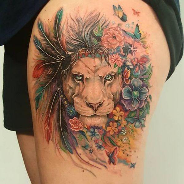 Татуировка в виде картины льва с разноцветными перьями
