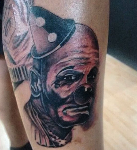 Расстроенный клоун на татуировке