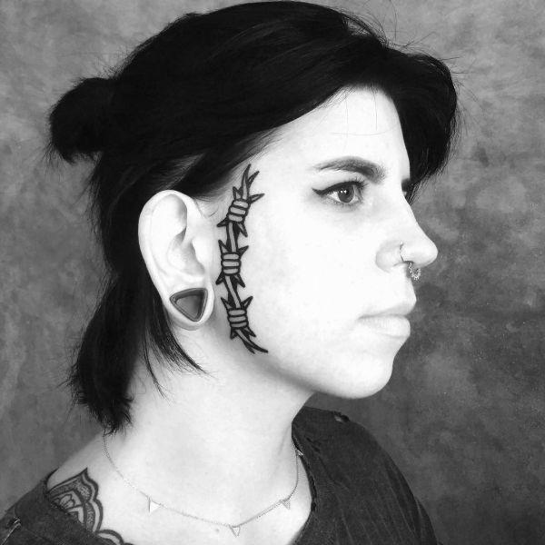 Татуировка колючей проволоки на лице девушки