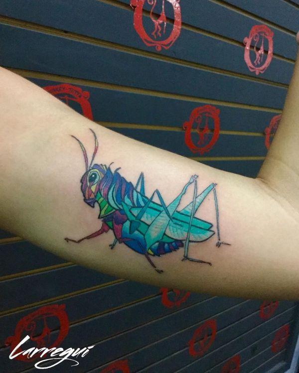 Разноцветный кузнечик в виде татуировки на руке