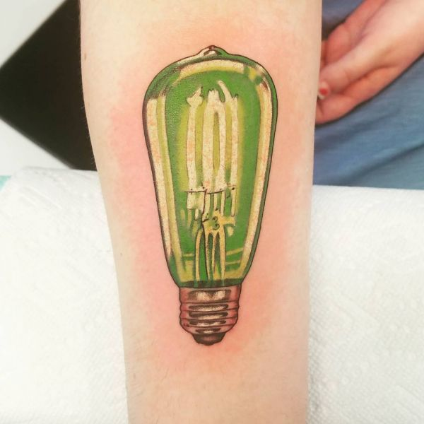 Татуировка зеленой ласпочки на предплечье у девушки