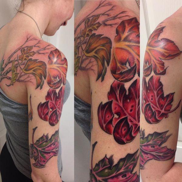 Татуировка красных и оранжевых листьев на плече у девушки
