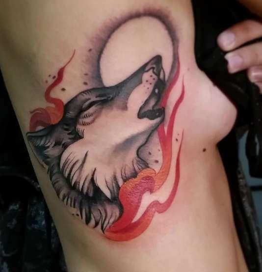 Татуировка в виде волка, воющего на луну