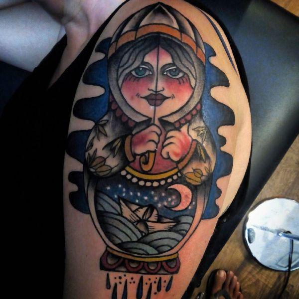 Необычная татуировка матрешки на плече парня