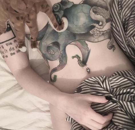 Осьминог в виде татуировки на животе у девушки