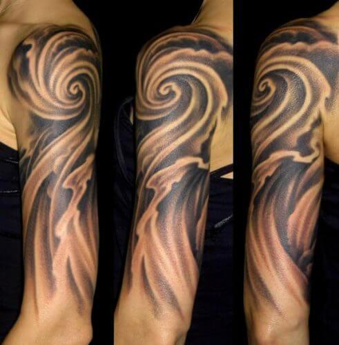 Ветер в виде черно-белой татуировки на плече девушки