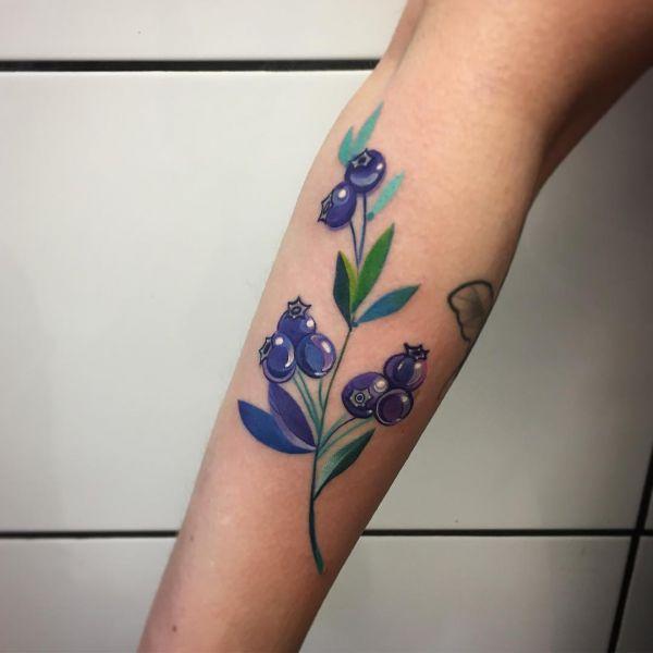 Татуировка черники на предплечье девушки в цвете