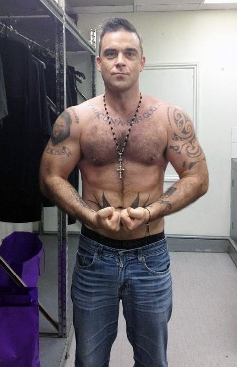 Робби Уильямс с татуировками перед зеркалом