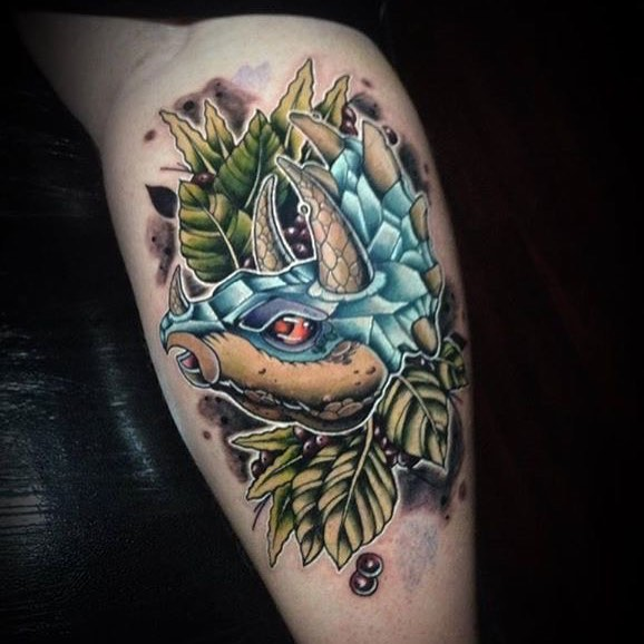 Татуировка динозавра на голени парня в цвете