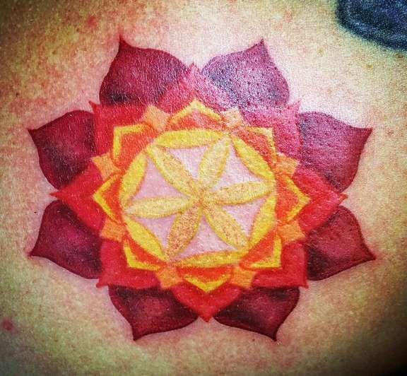 Красно-желтое солнце в виде цветка лотоса на спине