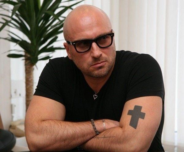 Татуировка у Дмитрия Нагиева в виде креста на руке, бицепсе