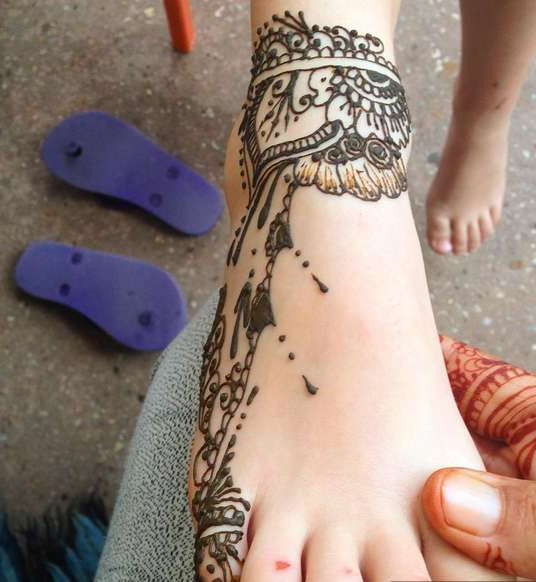 Татуировка хной на ноге девушки