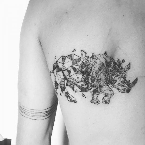 Носорог в виде татуировки в стиле геометрия на лопатке парня