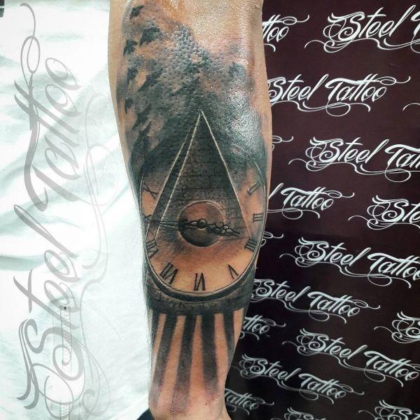 Татуировка пирамида с лучами солнца и часами