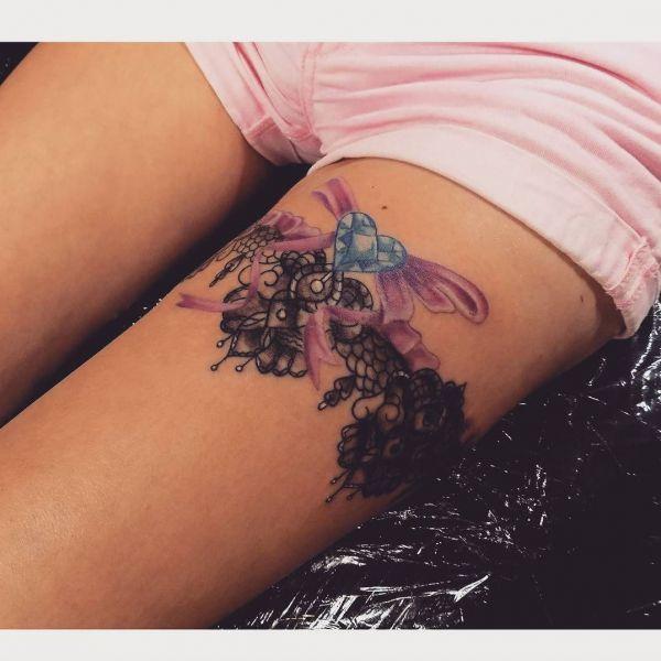 Подвязка с узорами и цветными крылышками и сердцем на ноге девушки