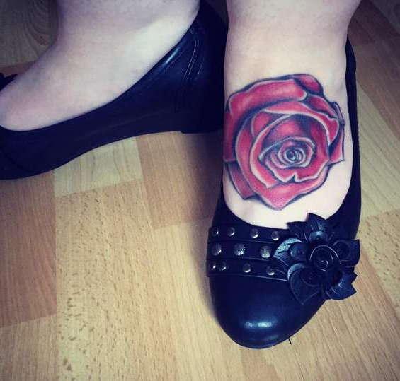 Красная роза на ноге дамы