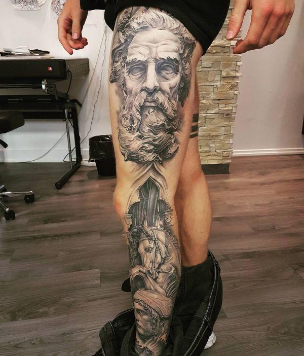 Татуировка бородатой скульптуры на ноге парня