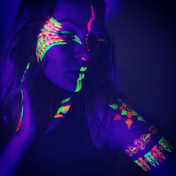 Ультрафиолетовые татуировки на лице и руке девушки