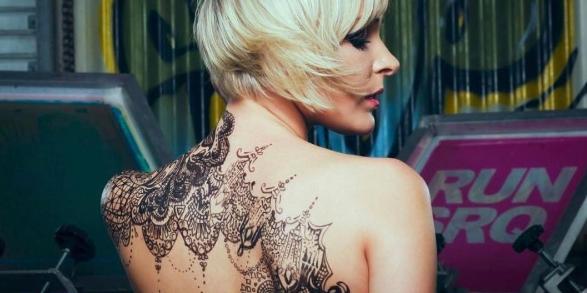 Татуировка кружева на спине девушки