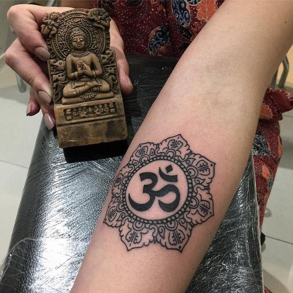 Знак Ом с мандалой на руке девушки