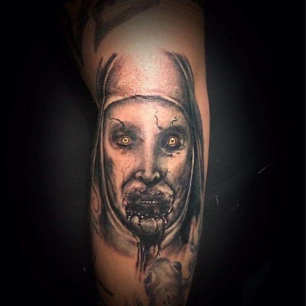 Татуировка зло на ноге в виде изображения лица бабушки