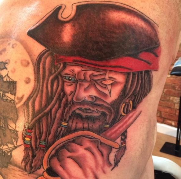 Пиратская татуировка на плече: пират с голубым глазом