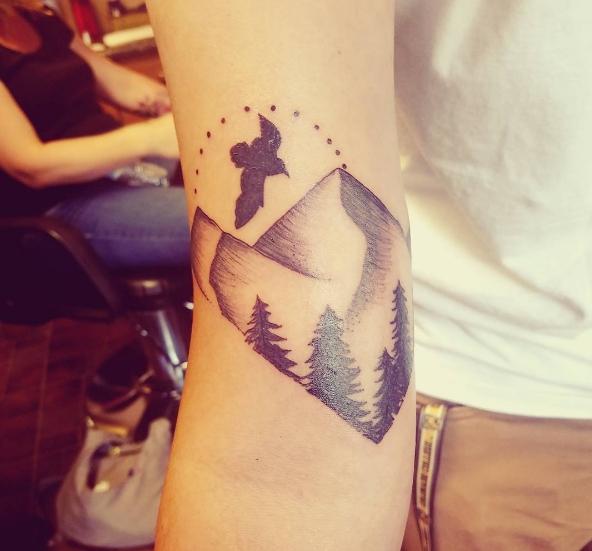 Татуировка на руке в виде природы с горами, деревьями и птицей