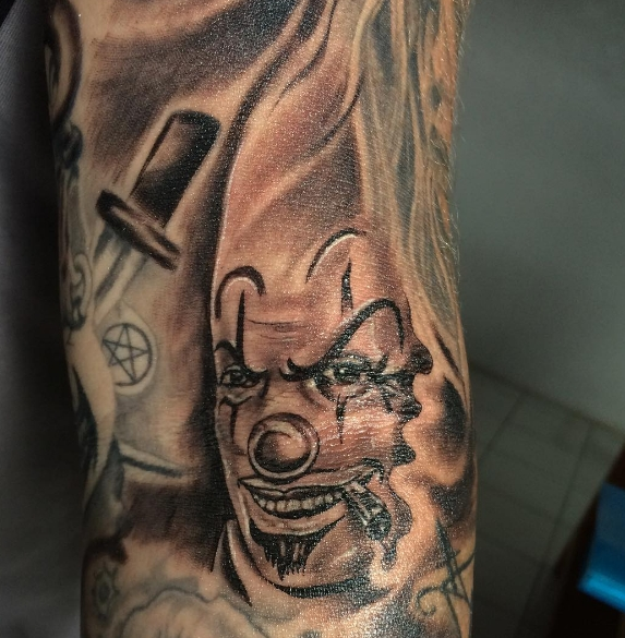Злой клоун с мечом и сигарой на татуировке