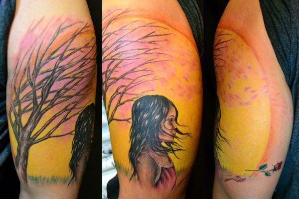 Девушка с деревом во время ветра - тату на бицепсе парня