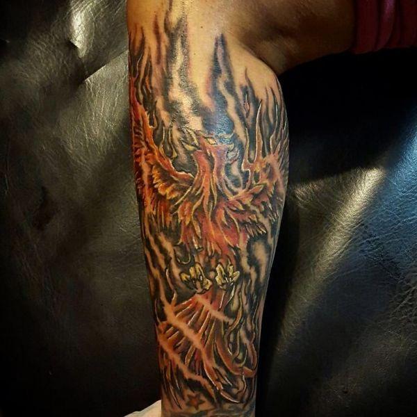 Татуировка с полыхающей жар птицей на ноге парня