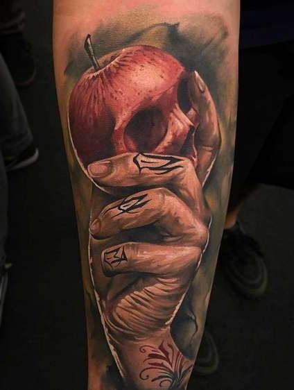 Татуировка на руке в виде руки, держащей яблоко