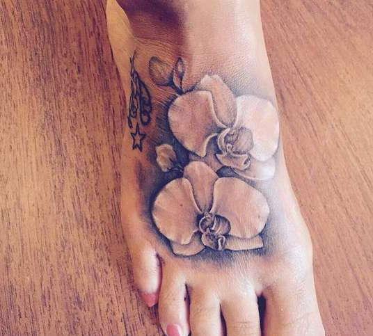 Белые цветочки на ступне девушки